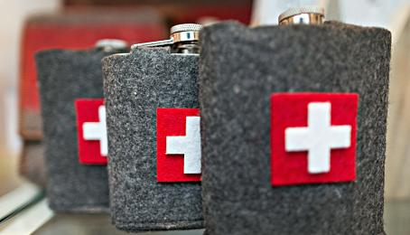 Swiss national flags sit on woolen hipflask covers on display in a souvenir shop in Zurich, Switzerland, on Wednesday, Nov. 9, 2016.