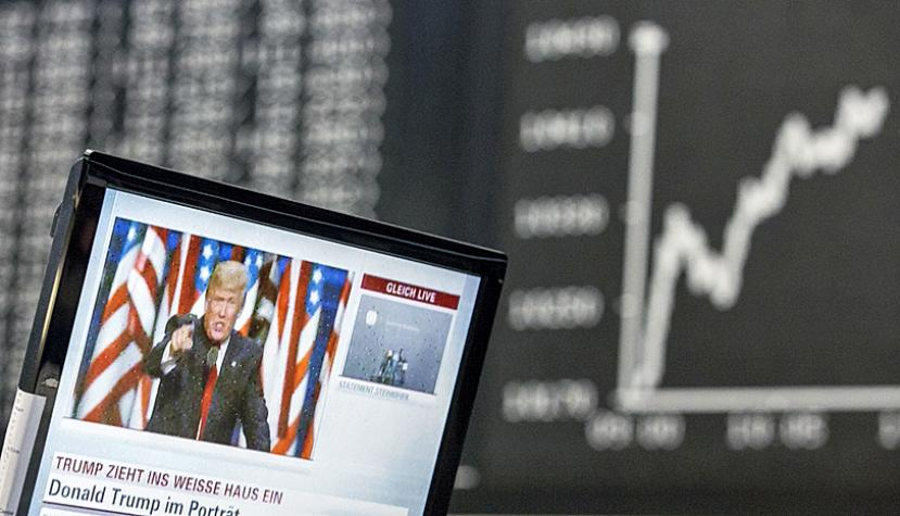 A television news report shows U.S. President-elect Donald Trump as the DAX Index curve shows market reaction inside the Frankfurt Stock Exchange in Frankfurt, Germany, on Wednesday, Nov. 09, 2016.