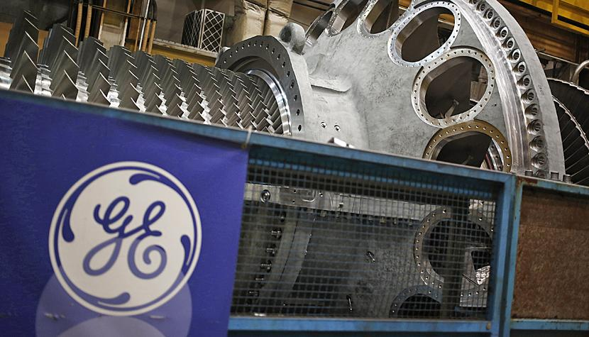 GE-Logo vor einer Gasturbine in einer Energieanlage in Greenville, South Carolina, USA (Jan. 2017)