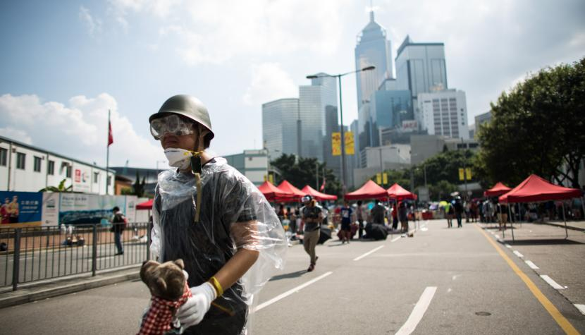 A demonstrator wears a disposable raincoat, helmet and goggles during a protest in Hong Kong, China, on Sunday, Sept. 28, 2014.